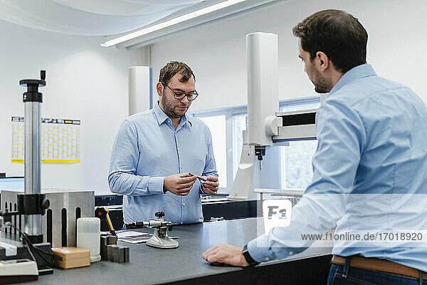 Ingenieure  die in einem Messraum im Büro stehen und Geräte prüfen
