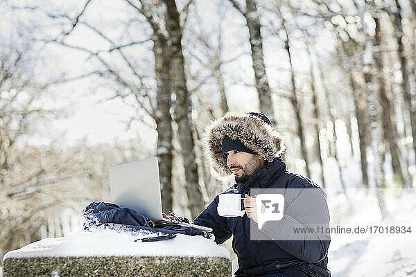 Geschäftsmann trinkt Kaffee und arbeitet an einem Laptop im Schnee