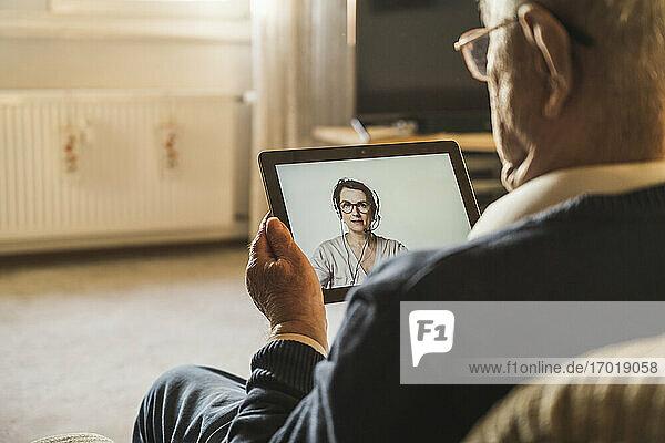 Ein älterer männlicher Patient lässt sich von einer Ärztin für Allgemeinmedizin per Videoanruf über ein digitales Tablet beraten. Ein älterer männlicher Patient lässt sich von einer Ärztin für Allgemeinmedizin per Videoanruf über ein digitales Tablet beraten.