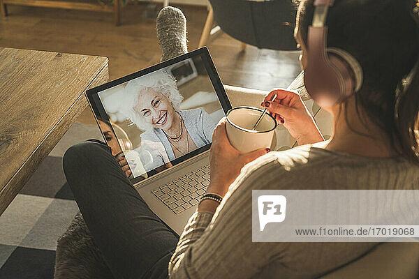 Ältere Frau lächelt während eines Videogesprächs auf dem Laptop-Bildschirm Ältere Frau lächelt während eines Videogesprächs auf dem Laptop-Bildschirm