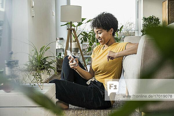 Frau lächelt  während sie ein Mobiltelefon benutzt und zu Hause sitzt Frau lächelt, während sie ein Mobiltelefon benutzt und zu Hause sitzt
