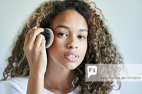 Young woman applying face powder with make-up brush against wall