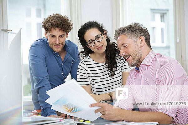 Smiling professional colleagues discussing in meeting at office