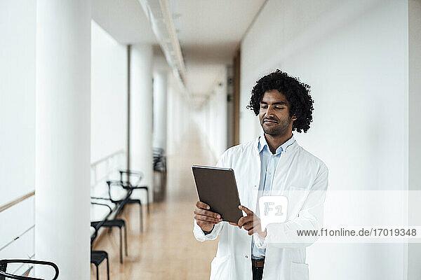 Selbstbewusster junger Arzt mit digitalem Tablet auf dem Krankenhausflur