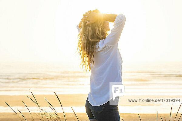 Frau mit Händen hinter dem Kopf stehend am Strand bei Sonnenuntergang Frau mit Händen hinter dem Kopf stehend am Strand bei Sonnenuntergang