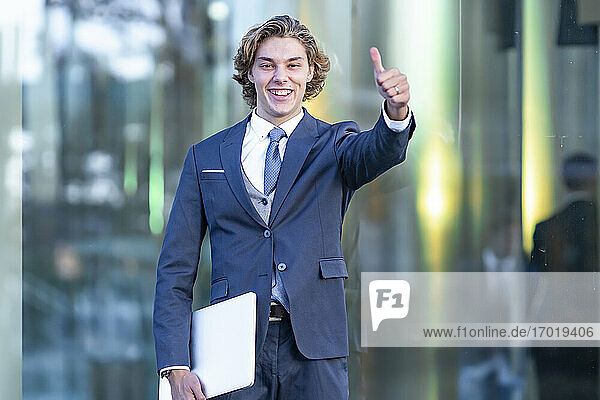 Male professional doing thumbs up while holding laptop against glass