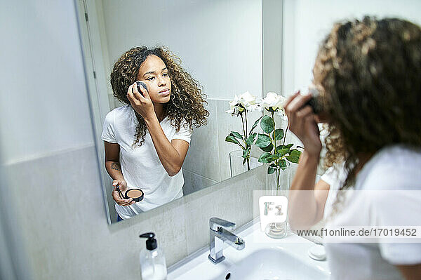 Young woman applying face powder with make-up brush while looking at mirror reflection in bathroom