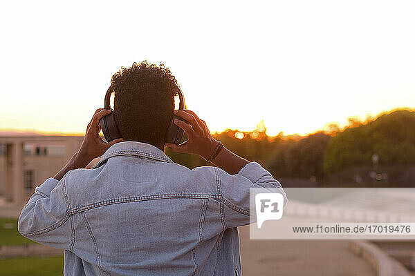 Young man listening music through headphones in park against clear sky during sunset