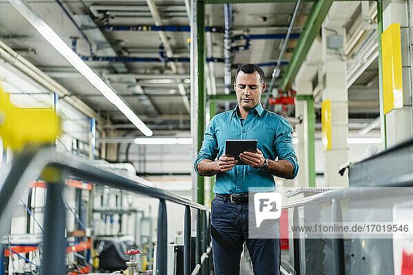 Männlicher Unternehmer  der bei der Arbeit in der Industrie ein digitales Tablet benutzt