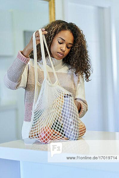 Junge Afro-Frau mit wiederverwendbarer Einkaufstüte in der Küche zu Hause Junge Afro-Frau mit wiederverwendbarer Einkaufstüte in der Küche zu Hause