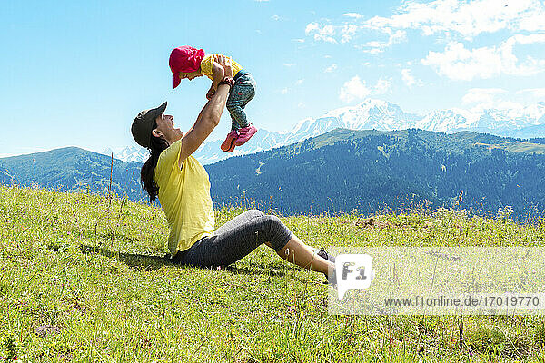Playful mother with her child playing over grass at Col des Aravis  Haute-Savoie  France