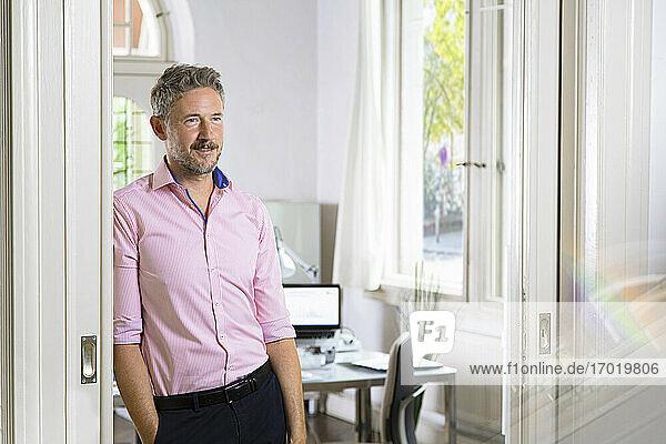 Male entrepreneur looking away while standing on doorway at office