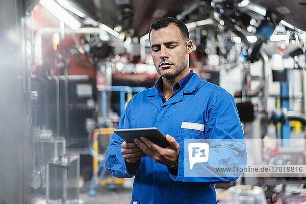 Ingenieur im blauen Kittel bei der Arbeit an einem digitalen Tablet in einer Fabrik