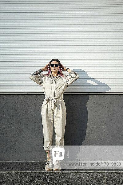 Stilvolle junge Frau mit Sonnenbrille an der Wand an einem sonnigen Tag Stilvolle junge Frau mit Sonnenbrille an der Wand an einem sonnigen Tag