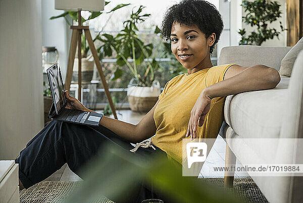 Junge Frau mit digitalem Tablet  lächelnd auf dem Sofa zu Hause lehnend Junge Frau mit digitalem Tablet, lächelnd auf dem Sofa zu Hause lehnend
