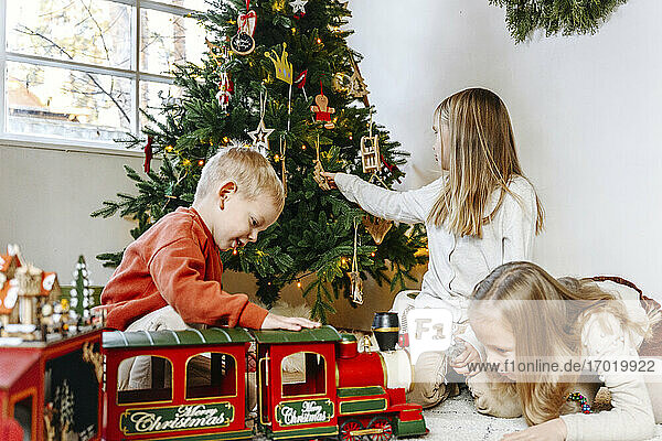 Siblings playing with toys at home during Christmas