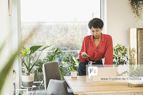 Frau schaut auf Smartphone am Tisch mit Laptop zu Hause Frau schaut auf Smartphone am Tisch mit Laptop zu Hause