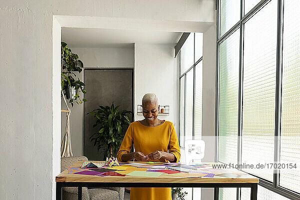 Origami-Künstlerin sitzt im Atelier und arbeitet mit buntem Papier Origami-Künstlerin sitzt im Atelier und arbeitet mit buntem Papier