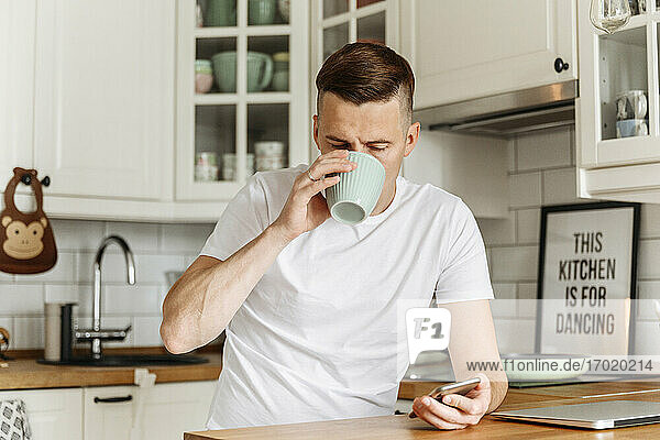 Man drinking from mug and holding smart phone in kitchen
