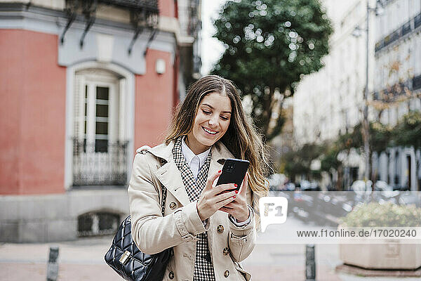 Happy woman carrying purse while using mobile phone in city