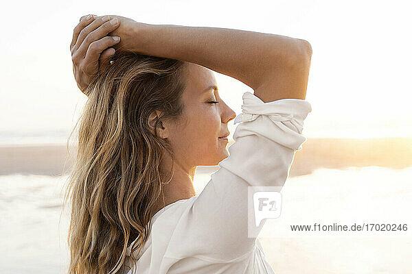 Mittlere erwachsene Frau mit geschlossenen Augen und Händen hinter dem Kopf stehend im Freien Mittlere erwachsene Frau mit geschlossenen Augen und Händen hinter dem Kopf stehend im Freien