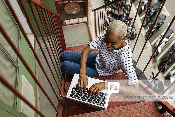 Kurzhaarige Frau sitzt auf einer Außentreppe und benutzt einen Laptop Kurzhaarige Frau sitzt auf einer Außentreppe und benutzt einen Laptop