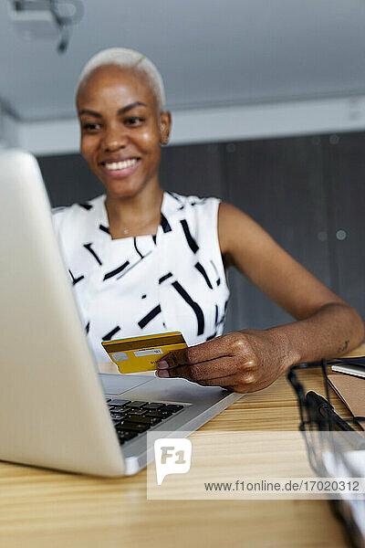 Geschäftsfrau  die im Büro sitzt und einen Laptop benutzt  um eine Online-Zahlung mit einer Kreditkarte vorzunehmen Geschäftsfrau, die im Büro sitzt und einen Laptop benutzt, um eine Online-Zahlung mit einer Kreditkarte vorzunehmen
