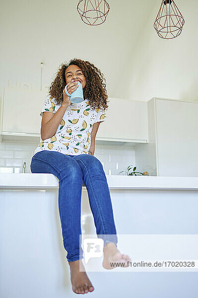 Smiling young woman with coffee cup on kitchen counter at home