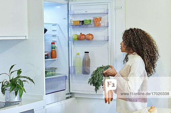Junge Afro-Frau  die zu Hause ein Bündel Karotten in den Kühlschrank legt Junge Afro-Frau, die zu Hause ein Bündel Karotten in den Kühlschrank legt