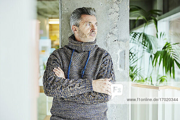 Man wearing turtleneck sweater leaning with arms crossed on pillar at office