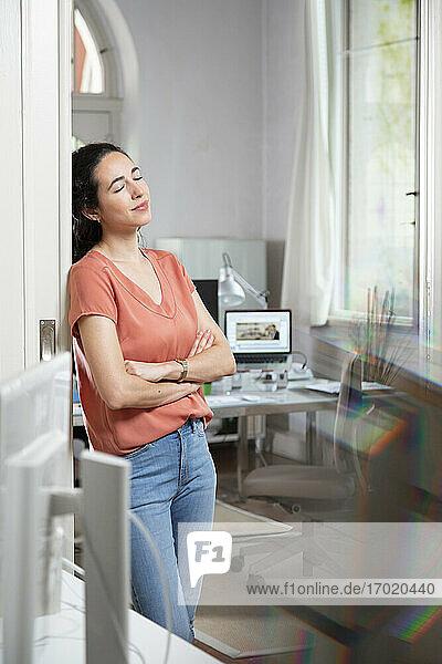 Female professional day dreaming while leaning on door at office