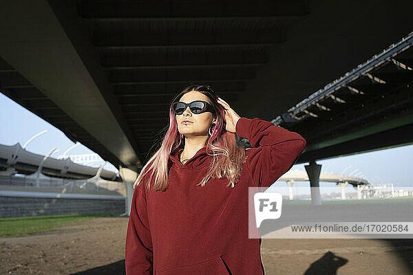Junge Frau mit Hand im Haar unter einer Brücke an einem sonnigen Tag Junge Frau mit Hand im Haar unter einer Brücke an einem sonnigen Tag