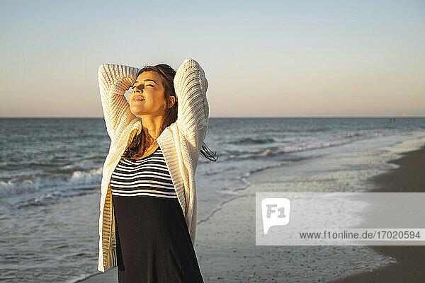 Lächelnde junge Frau am Strand gegen den klaren Himmel bei Sonnenuntergang Lächelnde junge Frau am Strand gegen den klaren Himmel bei Sonnenuntergang