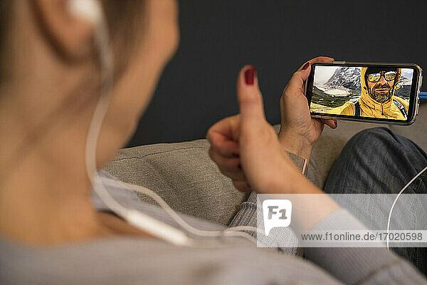 Reife Frau gestikuliert Daumen hoch zu Mann bei Videoanruf  während sie zu Hause sitzt Reife Frau gestikuliert Daumen hoch zu Mann bei Videoanruf, während sie zu Hause sitzt