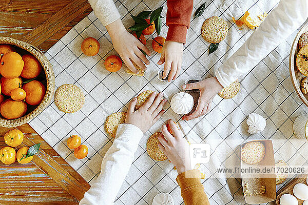 Hands of siblings taking cookies and tangerines on table at home