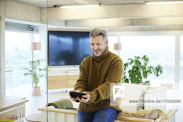Smiling man playing game on mobile phone while sitting at home