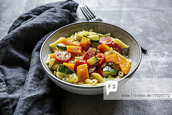 Bowl of vegan pasta with pumpkin  tomatoes and zucchini