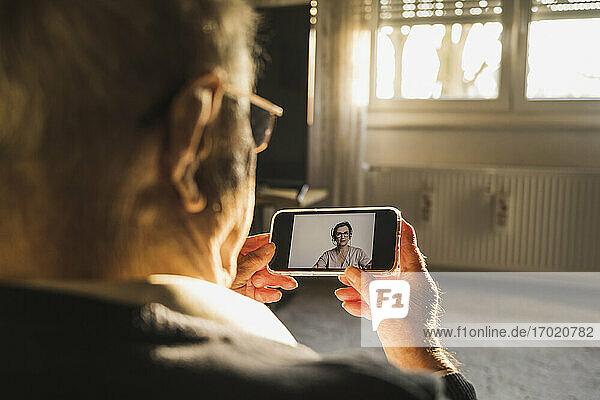 Ein älterer Mann lässt sich von einer Allgemeinmedizinerin per Videoanruf über ein Smartphone im Wohnzimmer beraten. Ein älterer Mann lässt sich von einer Allgemeinmedizinerin per Videoanruf über ein Smartphone im Wohnzimmer beraten.