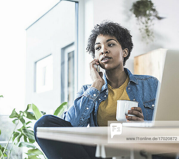 Woman talking on mobile phone  sitting in front of laptop at home