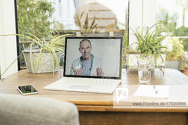 Smiling doctor on video call through laptop at home