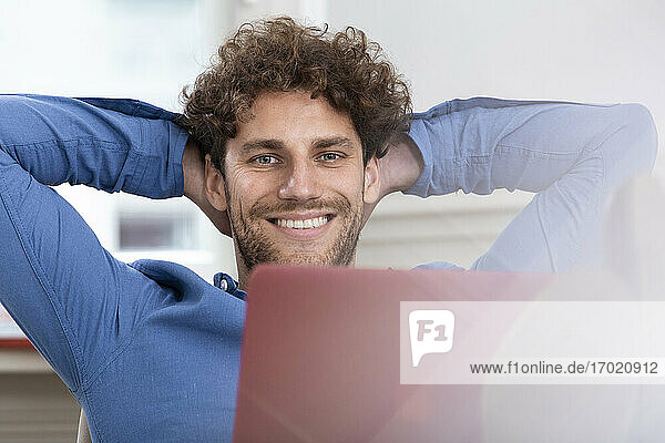 Smiling businessman with hands behind head working at office