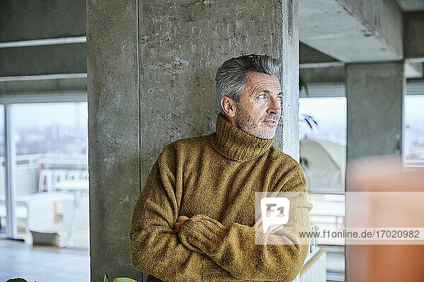 Mature man with arms crossed looking away while standing at office