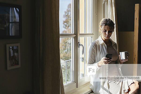 Schwangere Frau mit Kaffeetasse Textnachrichten auf Handy gegen Fenster