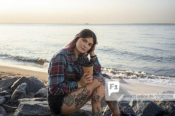 Hipster-Frau mit Hand im Haar  die einen wiederverwendbaren Kaffeebecher hält  während sie auf einem Felsen am Strand sitzt Hipster-Frau mit Hand im Haar, die einen wiederverwendbaren Kaffeebecher hält, während sie auf einem Felsen am Strand sitzt