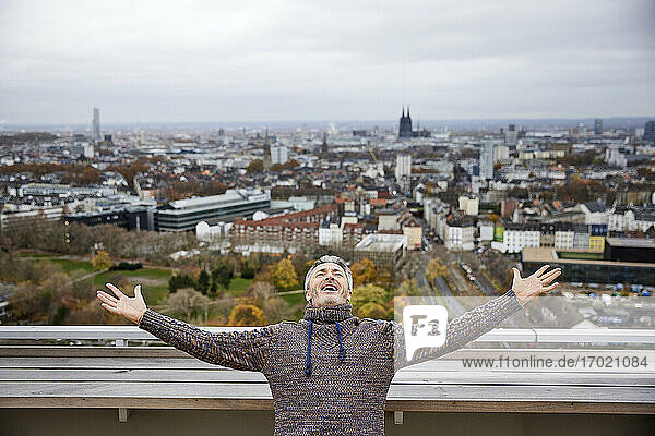 Mature man smiling while standing with arms outstretched on rooftop