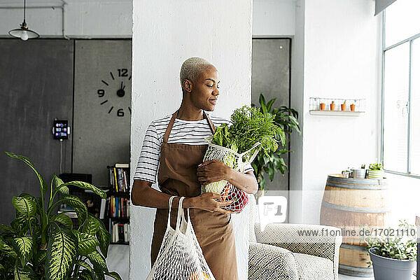 Hübsche Frau in Schürze trägt Netz mit frischem Gemüse Hübsche Frau in Schürze trägt Netz mit frischem Gemüse
