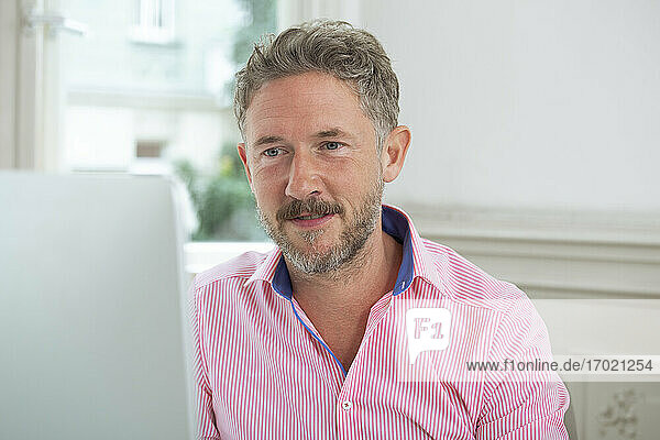 Mature male entrepreneur working on computer at office cabin