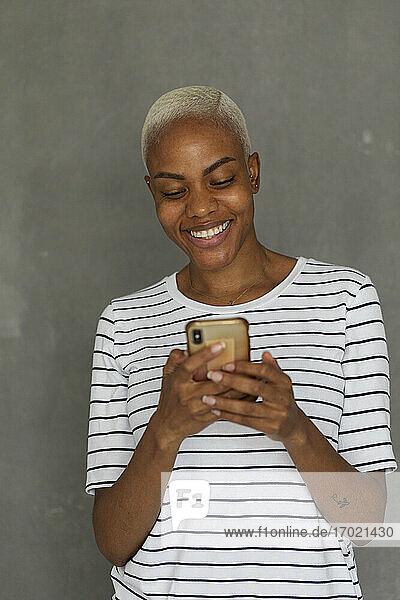 Lächelnde Frau mit gestreiftem Hemd vor grauem Hintergrund  die ein Smartphone hält Lächelnde Frau mit gestreiftem Hemd vor grauem Hintergrund, die ein Smartphone hält