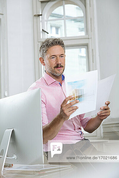 Male professional reading paper document by computer in office