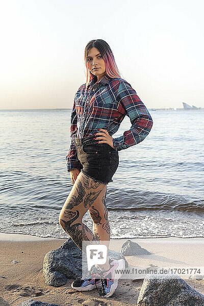 Stilvolle Frau mit Hand auf der Hüfte gegen das Meer am Strand Stilvolle Frau mit Hand auf der Hüfte gegen das Meer am Strand
